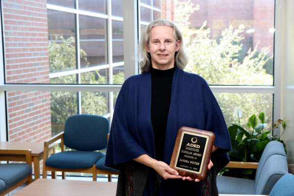 Dr. Sandra Winter holding 2020 ADED Scholar Award