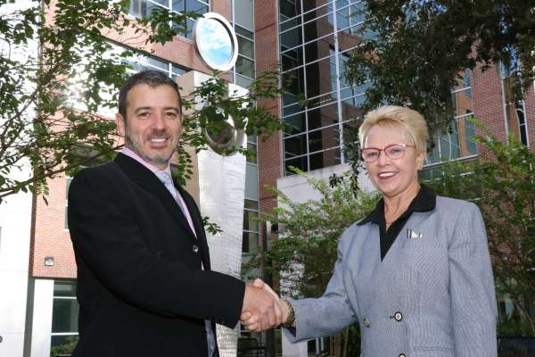 Drs. Classen and Romero shaking hands in front of HPNP building