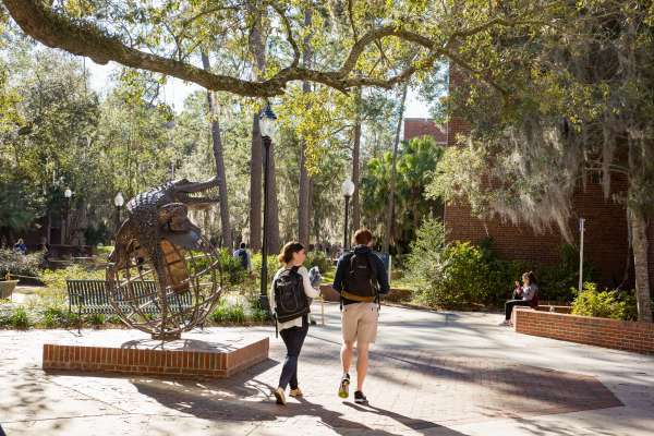 Two students walking on UF campus by a Gator sculpture