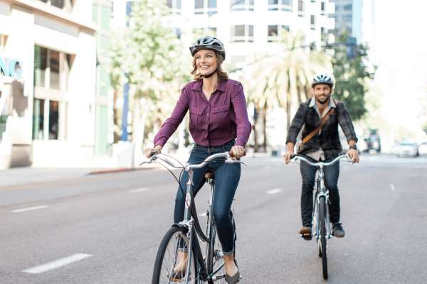 two smiling cyclists with helmets